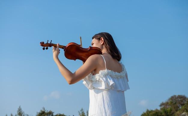 Hermosa chica asiática vestido blanco tocando un violín