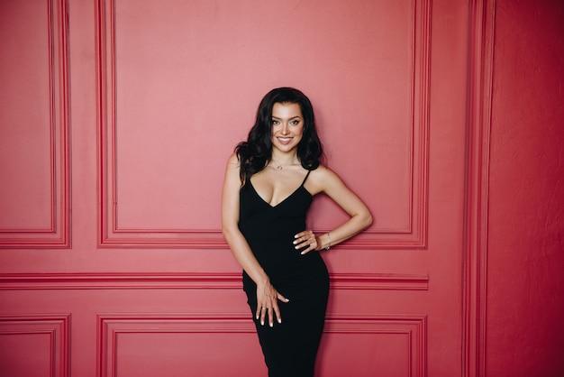 Hermosa chica de aspecto oriental. vestido ajustado negro en las correas.