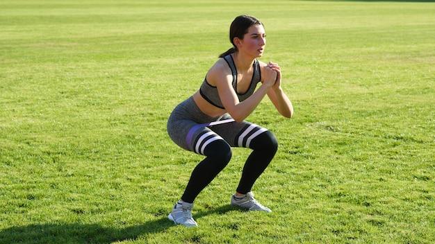 Hermosa chica atlética se agacha sobre la hierba en el estadio