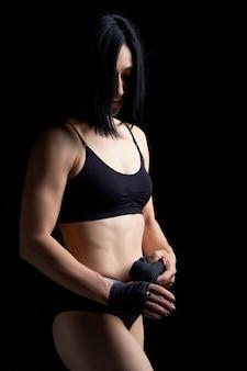 Hermosa chica atlética con cabello negro rebobina su mano con un vendaje elástico negro