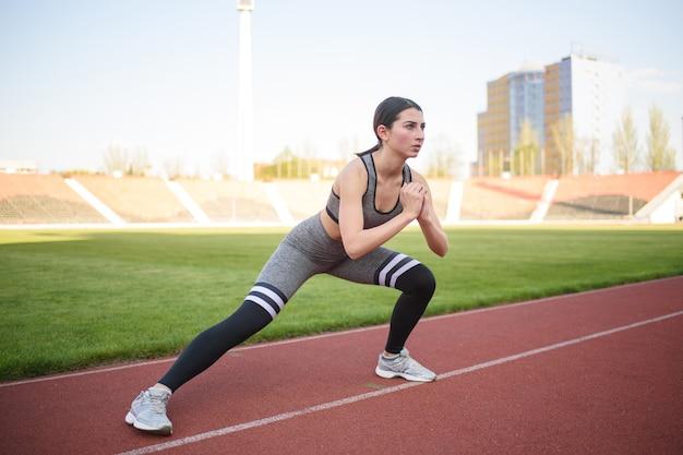 Hermosa chica atlética calentando antes de un duro entrenamiento en el estadio