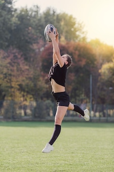 Hermosa chica atrapando una pelota de rugby