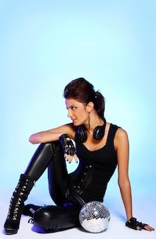 Hermosa chica con auriculares y bola de discoteca