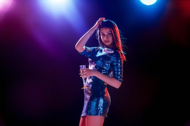 La hermosa chica bailando en la fiesta y bebiendo champaña