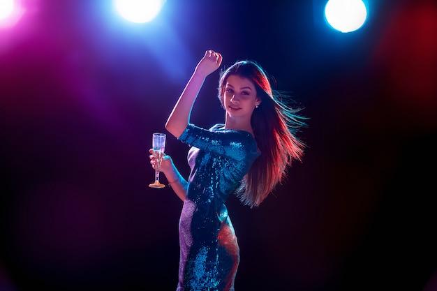 La hermosa chica bailando en la fiesta bebiendo champaña