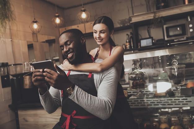 Hermosa chica barista abraza a un hombre sosteniendo una tableta