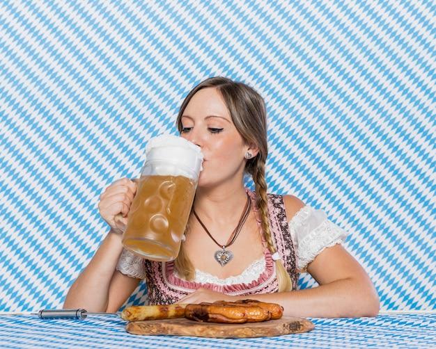 Hermosa chica bávara bebiendo cerveza
