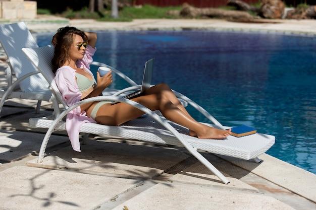 Hermosa chica bebe café cerca de la piscina