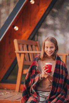 Hermosa chica con una bebida caliente disfrutando del día de otoño en la terraza