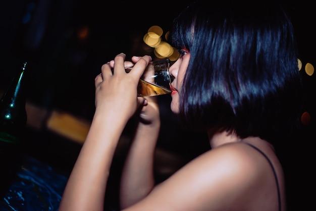 Hermosa chica bebiendo cerveza en un bar.