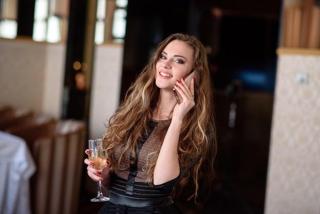 Hermosa chica bebiendo champán y hablando por teléfono en el restaurante