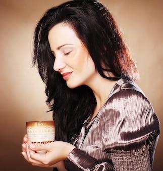 Hermosa chica bebiendo té o café.