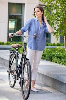 Hermosa chica con una bicicleta en el camino