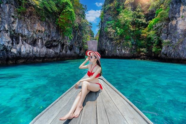 Hermosa chica en bikini rojo en barco en la isla de koh hong, tailandia.