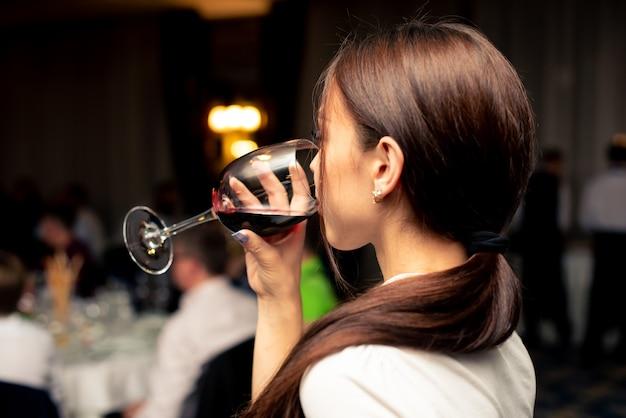 Hermosa chica en una blusa blanca está bebiendo vino con un vaso
