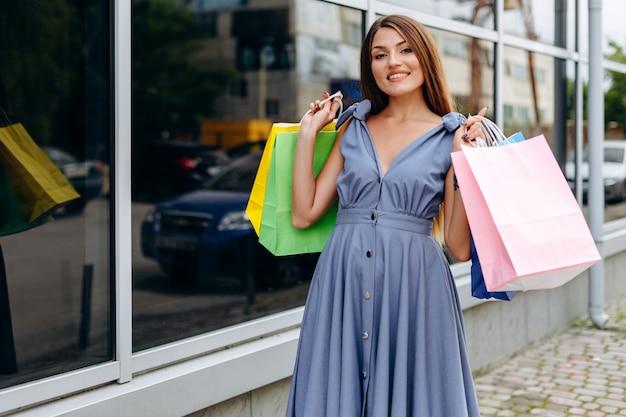 Hermosa chica con bolsas de colores caminando por el centro comercial