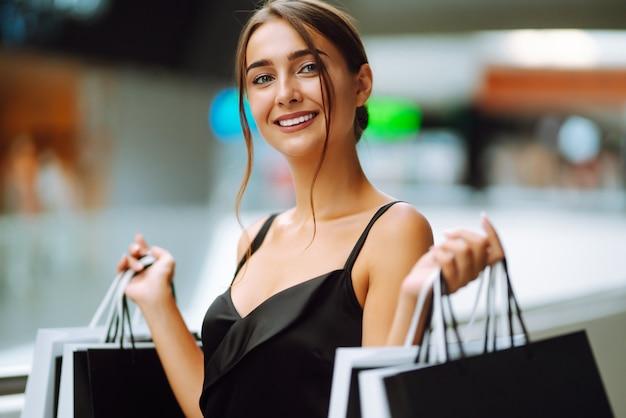 Hermosa chica con bolsas de compras mirando a la cámara y sonriendo mientras hace compras en el centro comercial