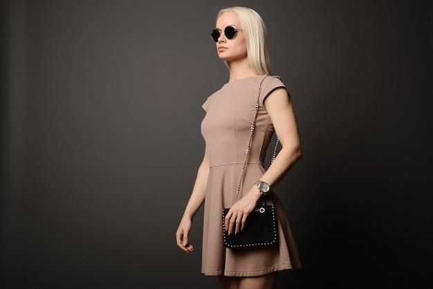 Hermosa chica con un bolso y gafas de sol