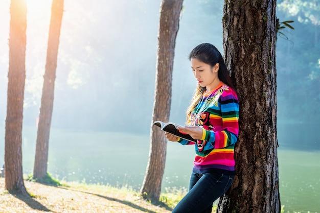 Hermosa chica en el bosque leyendo un libro.