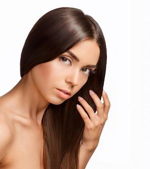 Hermosa chica con cabello castaño. cabello largo y liso brilla con salud