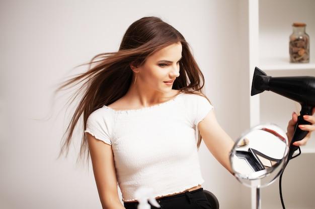 Hermosa chica con un cabello hermoso usa un secador de pelo