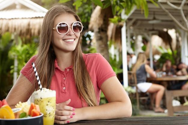 Hermosa chica con cabello largo desayunando en un café al aire libre en la playa durante las vacaciones en un país exótico.