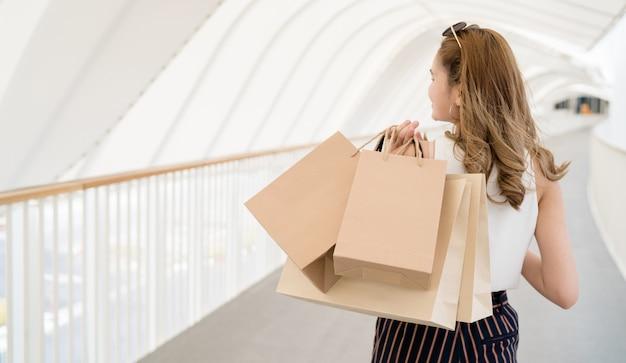 Hermosa chica de cabello largo ella está felizmente de compras en el centro comercial de la calle