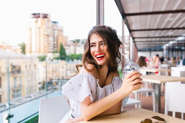 Hermosa chica con cabello largo está sentada a la mesa en la terraza de la cafetería. lleva un vestido blanco con hombros desnudos y lápiz labial rojo. ella sostiene la taza para ir y sonríe a un lado.