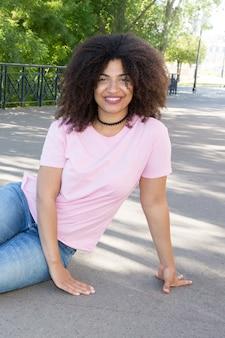 Hermosa chica con cabello rizado con una camiseta rosa y jeans azules