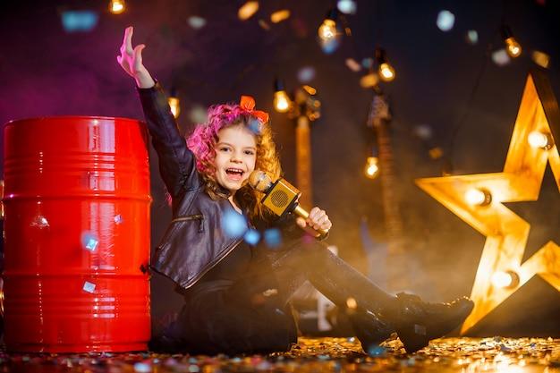 Hermosa chica con cabello rizado con chaqueta de cuero y gafas de sol rojas canta en un micrófono inalámbrico