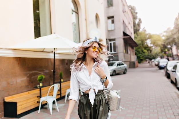 Hermosa chica con cabello rizado saludando caminando por la calle y mirando a su alrededor con una sonrisa