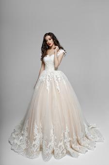 Hermosa chica con cabello rizado en vestido wendding, toca su cuello con la mano, aislado en un espacio en blanco.