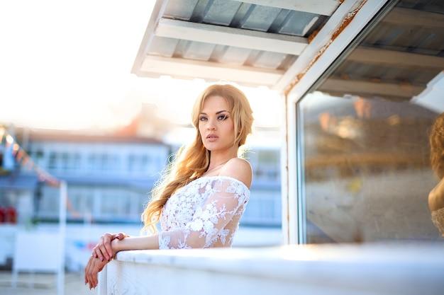 Hermosa chica con cabello rubio en elegante vestido de encaje posando besi