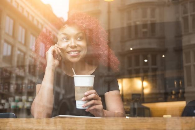 Hermosa chica en un café hablando por teléfono inteligente