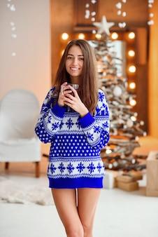 Hermosa chica en un cálido suéter de vacaciones con una taza de té caliente con canela