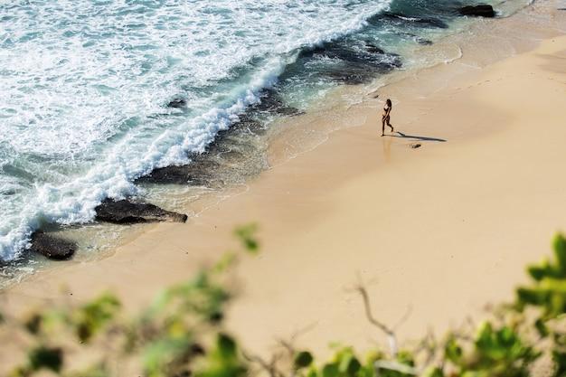 Hermosa chica camina por la playa salvaje. increíble vista superior.