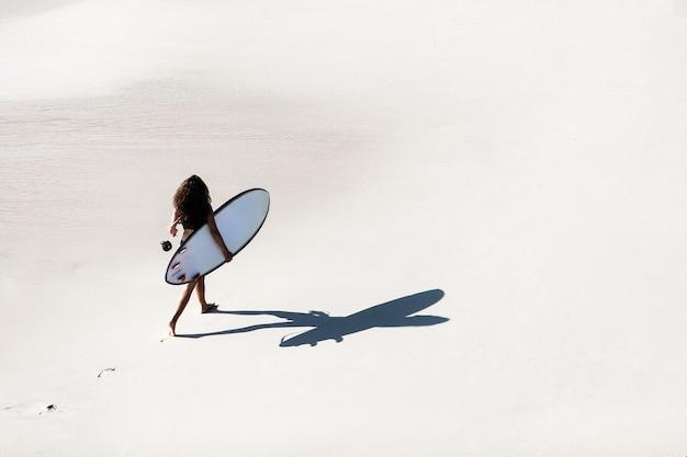 Hermosa chica camina con una tabla de surf en una playa salvaje. increíble vista desde la cima.