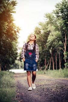 Hermosa chica caminando en un bosque de verano.