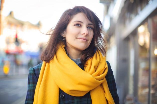 Hermosa chica caminando en la calle, vistiendo una bufanda amarilla
