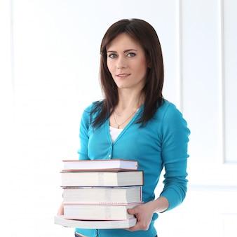 Hermosa chica con camiseta azul y libros