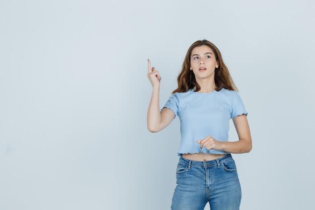 Hermosa chica en camiseta, jeans apuntando hacia arriba y mirando inteligente, vista frontal.