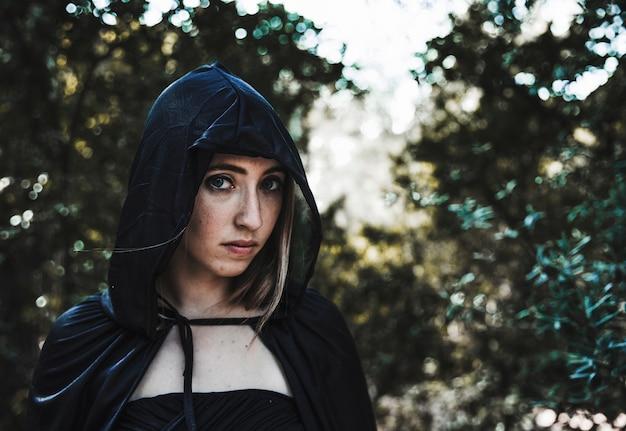 Hermosa chica en campana en el bosque