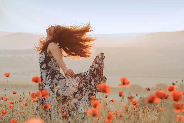 Hermosa chica en un campo de amapolas al atardecer. concepto de libertad