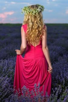 Hermosa chica en campo de lavanda al atardecer. mujer bonita estilo provenzal en un vestido y corona de flores