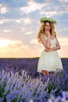 Hermosa chica en campo de lavanda al atardecer en vestido blanco y corona de flores