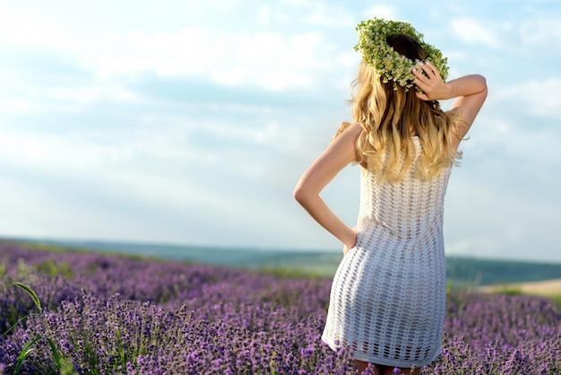 Hermosa chica en campo de lavanda. mujer bonita estilo provenzal en vestido blanco y corona de flores