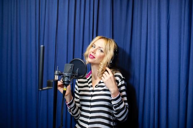 Hermosa chica cantando en un estudio de grabación