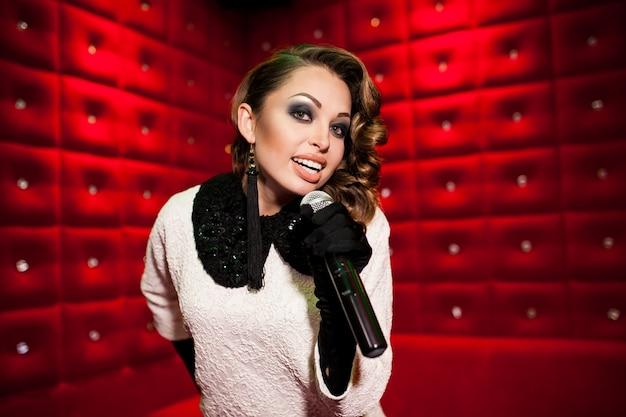 Hermosa chica cantando karaoke en una discoteca