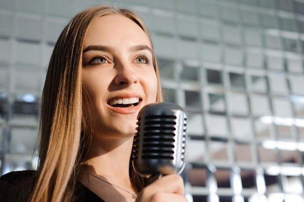 Hermosa chica cantando. mujer de belleza con micrófono.