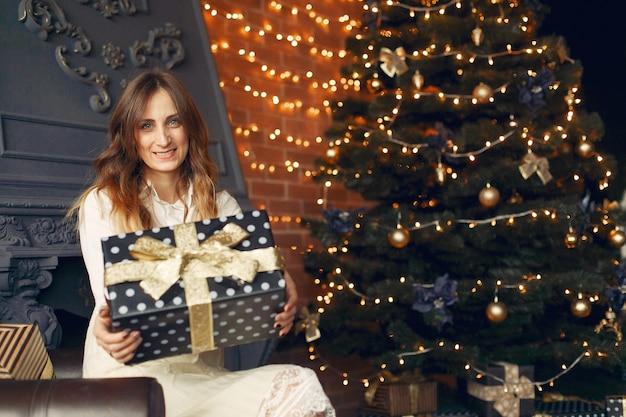 Hermosa chica en casa cerca del árbol de navidad